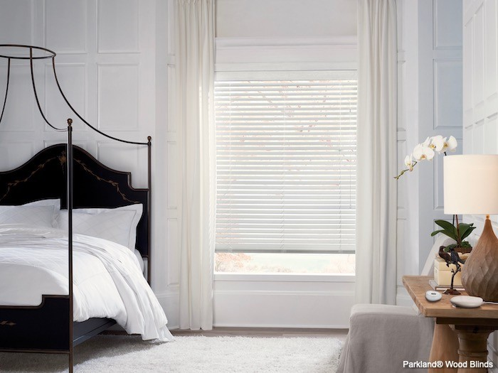 A bedroom with white walls, bedding and window coverings with a black bed.